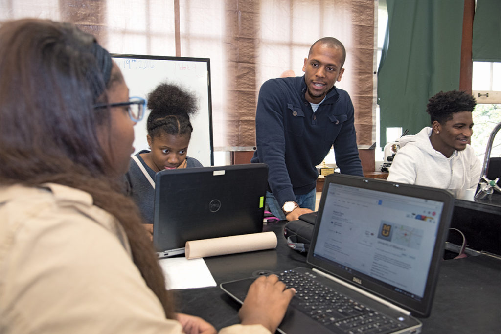 Mentor Jeffrey Gamble (center), a doctoral candidate in biomedical engineering, interacts with students at Soldan International Studies High School. YSP Continuing Mentor volunteers meet regularly with students during all four years of high school.