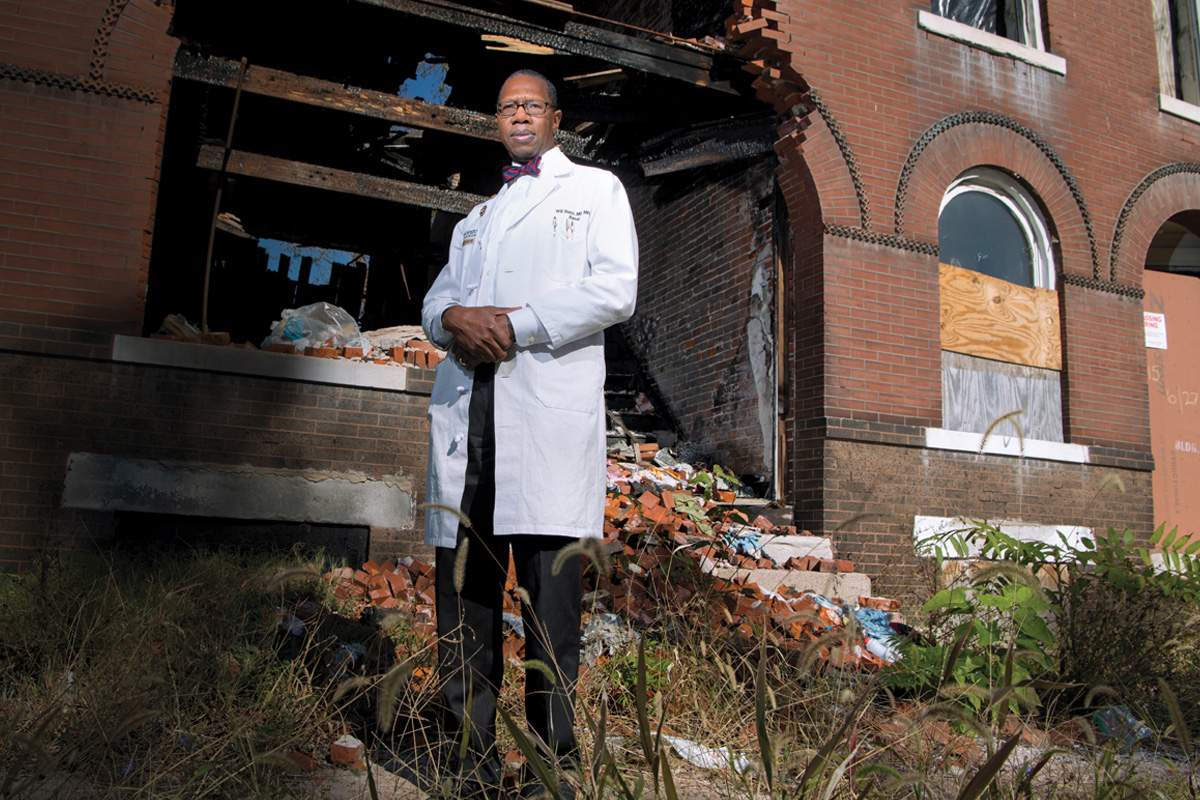 Will Ross stands in front of a dilapidated building in St. Louis.