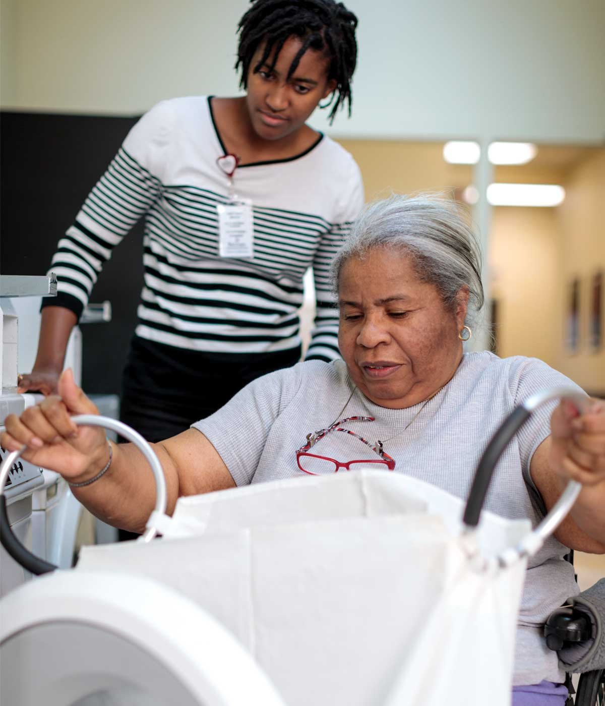 Showing a patient how to transport laundry to her home laundry room.